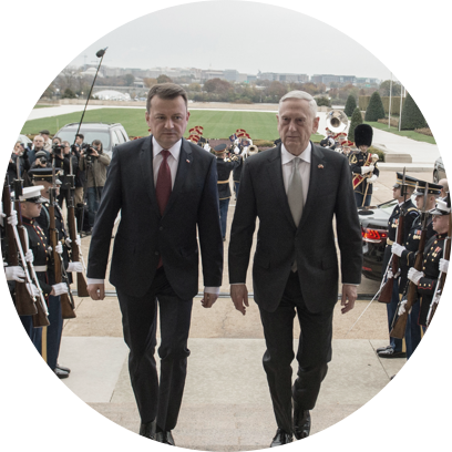 Polish Defense Minister Mariusz Blaszczak and former US Defense Secretary James Mattis walk flanked by soldiers at attention.