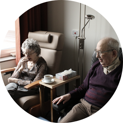Two elderly people share coffee near a subtle medical alert button.